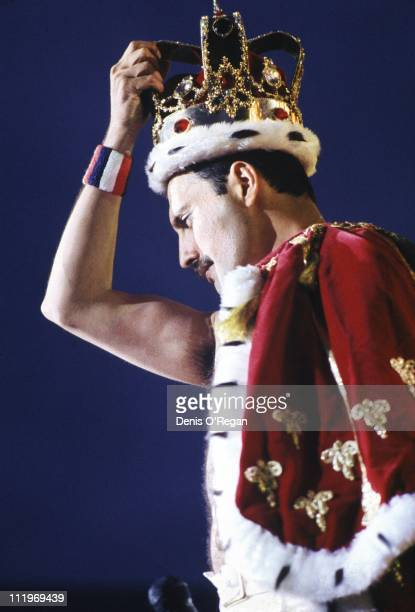 Singer Freddie Mercury wearing a crown during a performance with British rock group Queen 1986