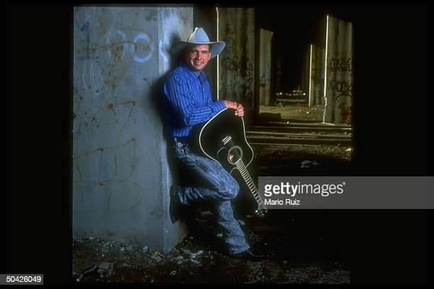 C/W singer Garth Brooks wearing cowboy hat and holding black acoustic guitar