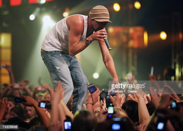 Singer Gentleman reaches down to fans from the stage as he performs during The Dome 42 music show at the TUI Arena on May 25 2007 in Hanover Germany
