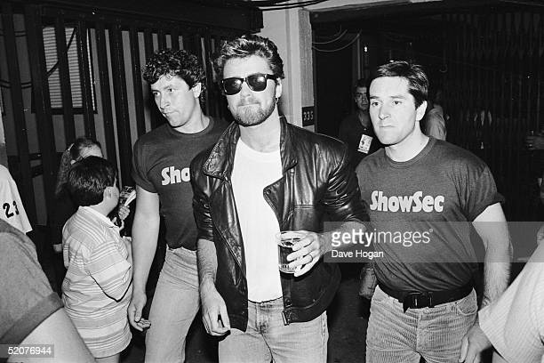 Singer George Michael is escorted by security backstage at Wembley Stadium during the Live Aid Concert 13th July 1985