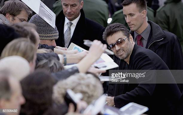 Singer George Michael signs autographs for fans as he arrives for the George Michael A Different Story World Premiere at Kino International during...