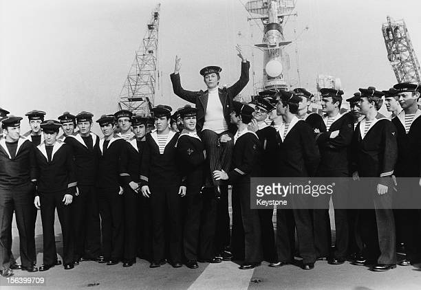 Singer Georgette Plana with a group of sailors on board the French helicopter cruiser 'Jeanne d'Arc' as it leaves Brest in France 29th October 1973...