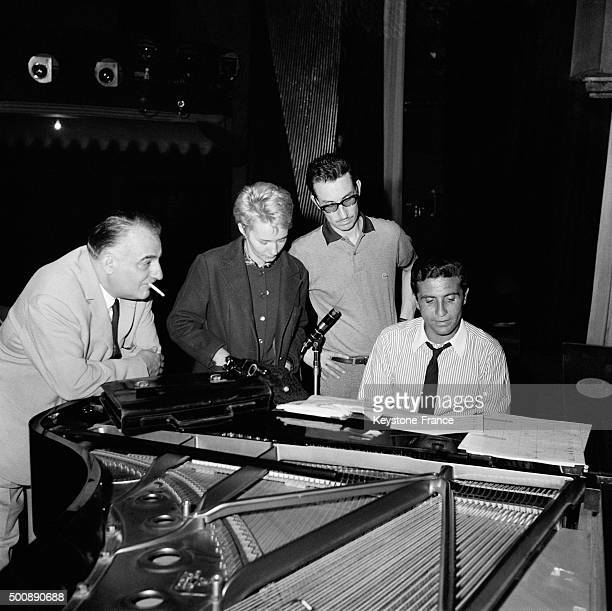 Singer Gilbert Bécaud rehearsing his new recital on stage at the Olympia Music Hall with director Bruno Coquatrix and lyric writer Claudine Coppin on...