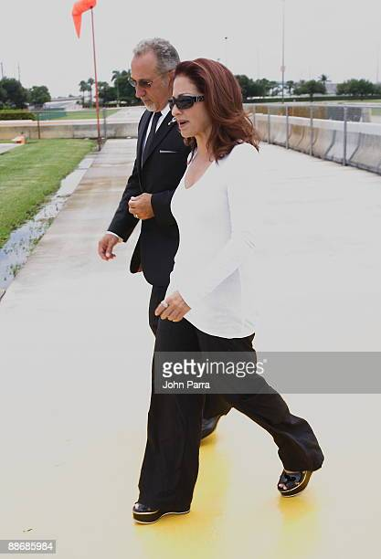 Singer Gloria Estefan and Emilio Estefan walk to waiting helicopter after a press conference to announce their investment in Miami Dolphins at Land...