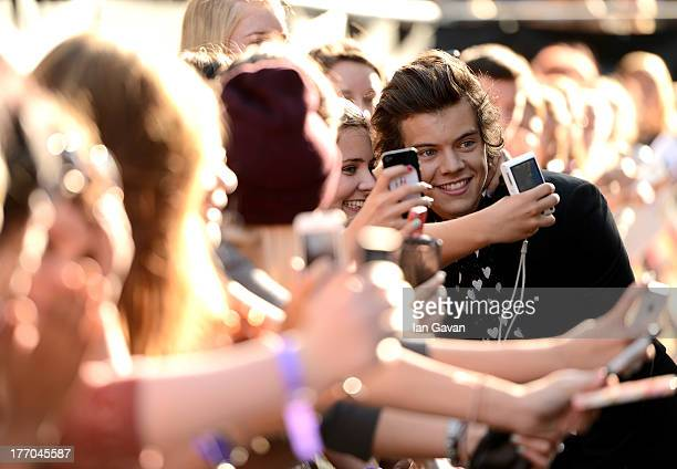Singer Harry Styles from One Direction poses with fans as he attends the One Direction This Is Us world premiere at the Empire Leicester Square on...