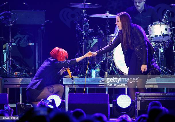 Singer Hayley Williams of Paramore performs with a fan onstage during 1061 KISS FM's Jingle Ball 2013 at Comcast Arena at Everett on December 8 2013...
