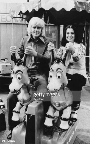 Singer Howard Carpendale rides a coinoperated donkey with a hostess of an automaton exhibition in Dusseldorf Germany 25th October 1973