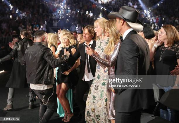 Singer Howie D of the Backstreet Boys greets singer Keith Urban while singer Carrie Underwood actor Nicole Kidman and singer Tim McGraw attend the...