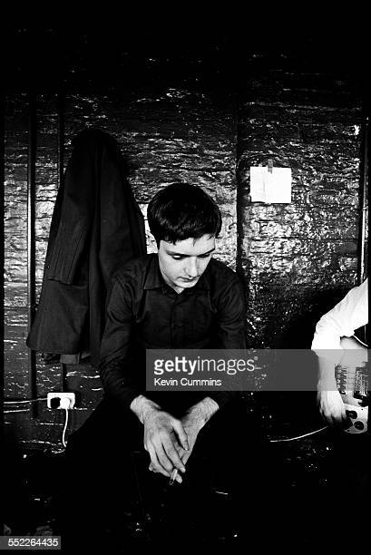 Singer Ian Curtis of rock group Joy Division, at TJ Davidson's rehearsal room, Little Peter Street, Manchester, 19th August 1979. On the right is...
