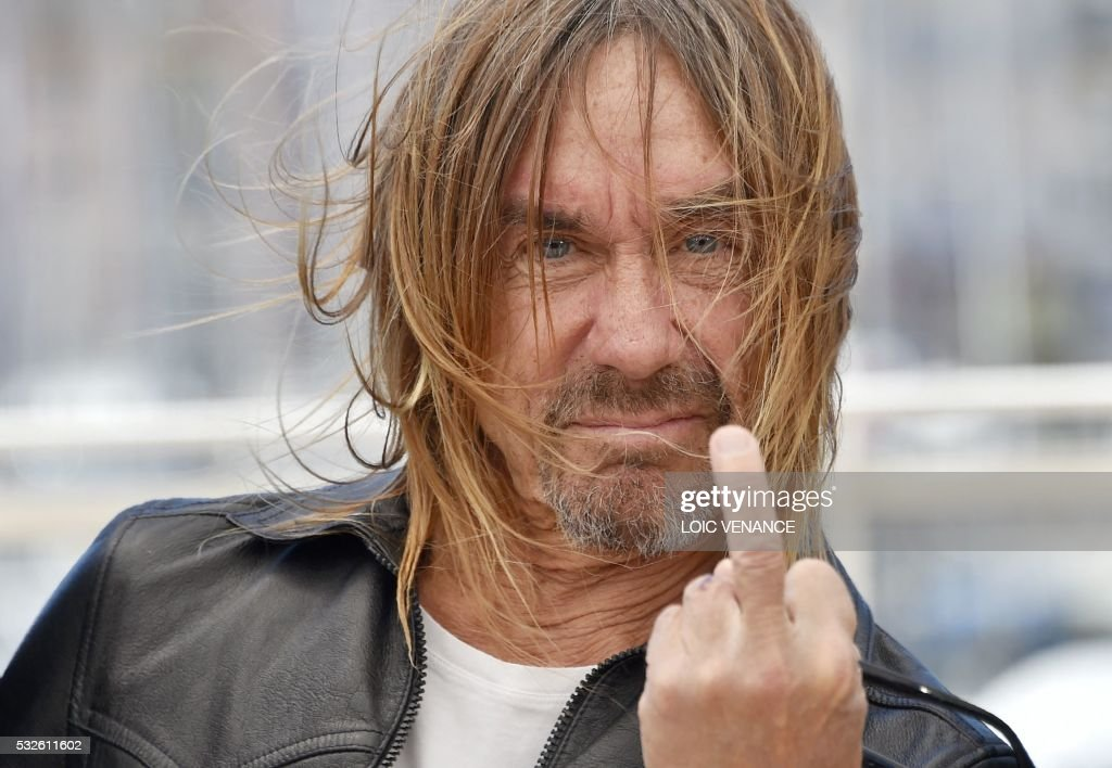 TOPSHOT - US singer Iggy Pop gives the fingers while posing on May 19, 2016 during a photocall for the film 'Gimme Danger' at the 69th Cannes Film Festival in Cannes, southern France. / AFP / LOIC