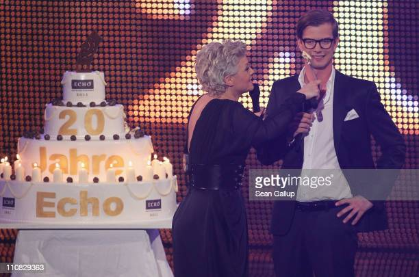 Singer Ina Mueller dabs Joko Winterscheidt with cake marking the 20th year of the Echo music awards at the Echo Awards 2011 at Palais am Funkturm on...