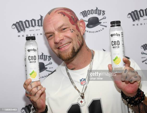 Singer Ivan Moody of Five Finger Death Punch displays CBD water bottles during an appearance to celebrate the release of Moody's Medicinals his new...
