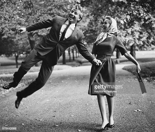 Singer Jackie Rae and his wife actress Janette Scott joking around as they walk through Hyde Park during a break in rehearsals for the pantomime...