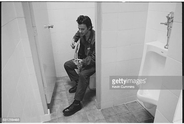 Singer James Dean Bradfield, of Welsh alternative rock group the Manic Street Preachers, playing a guitar while sitting on a lavatory, Bangkok,...