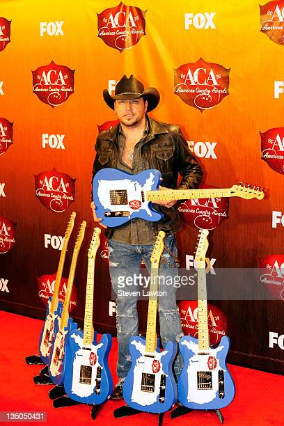 Singer Jason Aldean poses in the press room with the awards for Artist of the Year, Album of the Year, Singer of the Year; Male, Single of the Year;...