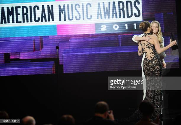 Singer Jennifer Lopez accepts Favorite Latin Music Artist award from actress Jennifer Morrison onstage at the 2011 American Music Awards held at...