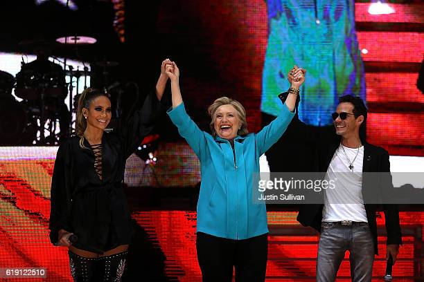 Singer Jennifer Lopez Democratic presidential nominee former Secretary of State Hillary Clinton and singer Marc Anthony raise their arms during a Get...