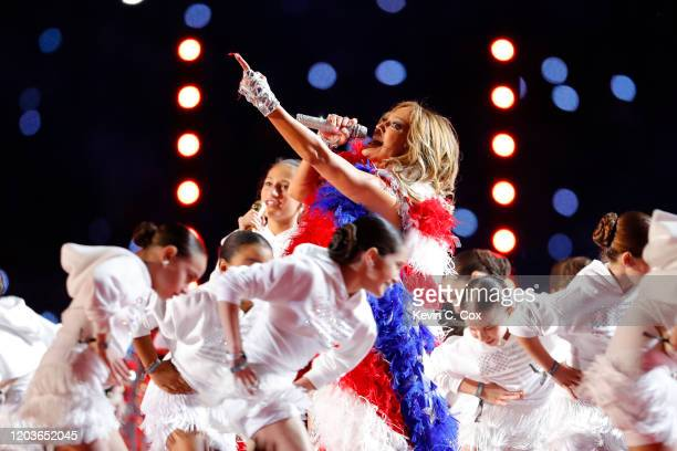 Singer Jennifer Lopez performs with her daughter Emme Maribel Muñiz while a Puerto Rican flag is displayed on stage during the Pepsi Super Bowl LIV...