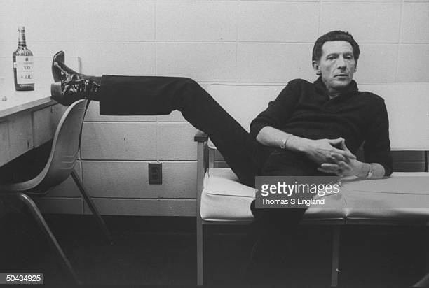 Singer Jerry Lee Lewis lounging on couch w one foot up on dressing table next to a bottle of Seagram's VO whiskey in dressing room at Performing Arts...