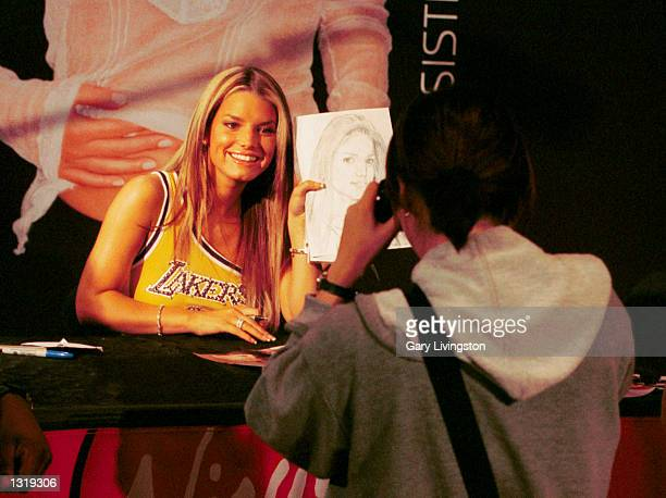 Singer Jessica Simpson holds up a portrait of herself drawn by a fan during the CD signing release of her new CD Irresistible June 6 2001 at Virgin...