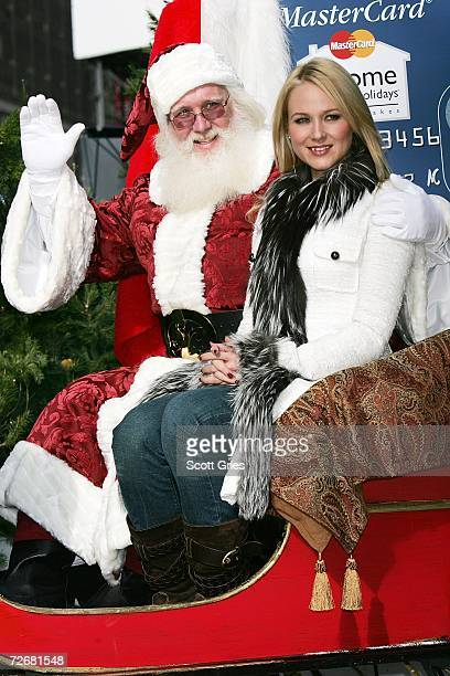 Singer Jewel poses for a photo with Santa Claus following a concert as part of the kick off for MasterCard's Home For The Holidays in Herald Square...