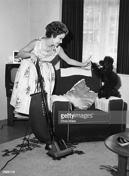 Singer Jill Westlake hoovers her living room in Westgate near Margate whilst telling off her poodle Bean for interrupting September 1958