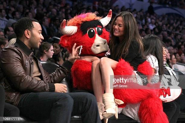 Singer John Legend Chicago Bulls mascot 'Benny the Bull' and model Christine Teigen speak during the 2011 NBA AllStar game at Staples Center on...