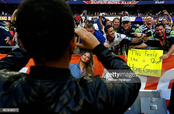 Singer John Legend takes a picture of girlfriend Chrissy Teigan on the fiield prior to Super Bowl XLIX at University of Phoenix Stadium on February 1...