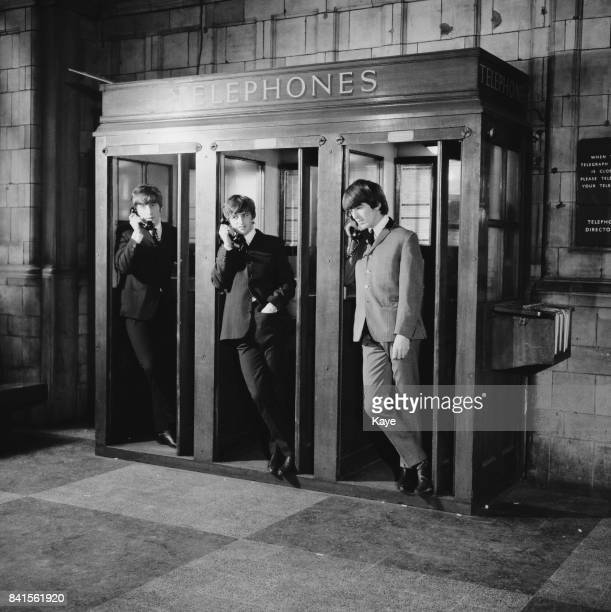 Singer John Lennon drummer Ringo Starr and guitarist George Harrison in telephone kiosks at Marylebone Station while filming musical comedy film 'A...