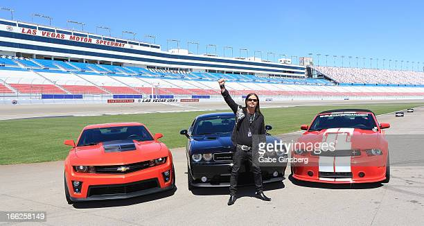Singer John Payne from the show 'Raiding The Rock Vault' poses in front of Chevrolet Camero ZL1 Dodge Challenger SRT8 392 and a Ford Mustang Shelby...
