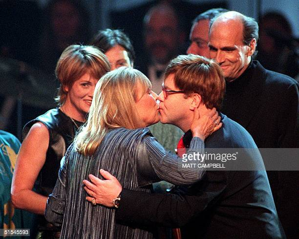 Singer Joni Mitchell gets a kiss from Elton John as singers Shawn Colvin and James Taylor watch after the finale of Turner Network Television's...