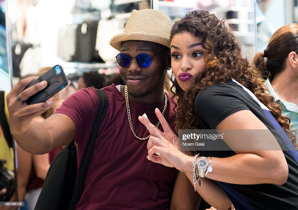 Singer Jordin Sparks (R) poses for a selfie with a fan on the set of 'Extra' at their New York studios at H&M in Times Square on August 25, 2015 in New York City.