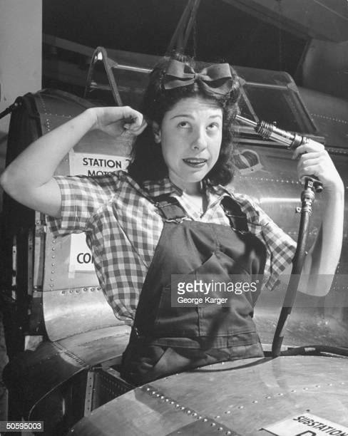 Singer Judy Canova holding drill gun to head at wing construction station during WWII