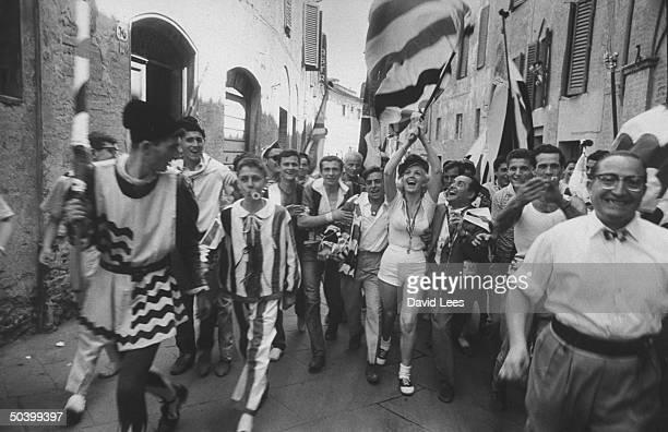 Singer Juli Reding carrying an Italian flag as she walks down the street with a group of fans