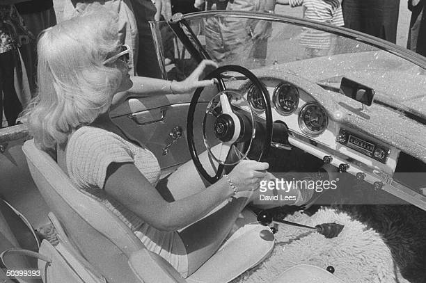Singer Juli Reding driving in her car through a crowded street of fans