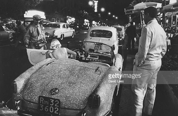 Singer Juli Reding getting out of her glitter painted car with appreciative men watching