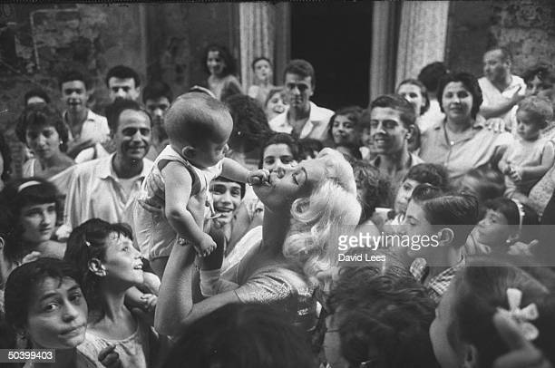 Singer Juli Reding holding and kissing a baby while fans crowd around her