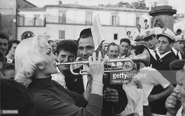 Singer Juli Reding learning how to play a trumpet while appreciative males look on during her visit