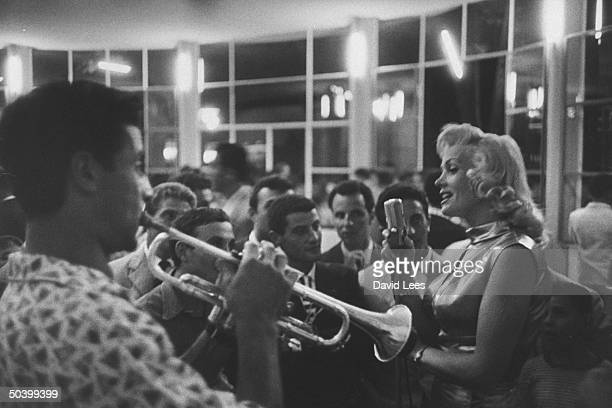 Singer Juli Reding singing for a group of fans as a man plays the trumpet