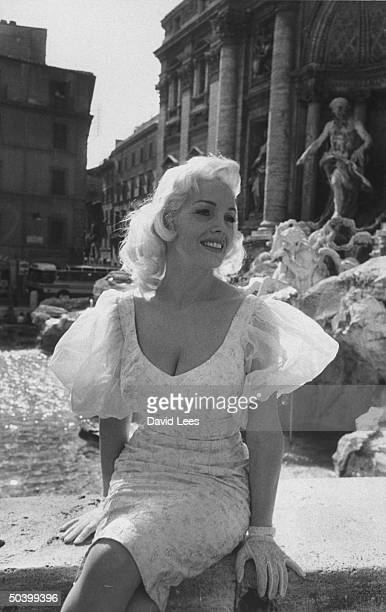 Singer Juli Reding sitting in front of a water fountain during her visit