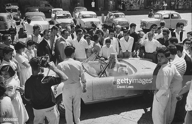 Singer Juli Reding sitting in her car surrounded by fans during her visit