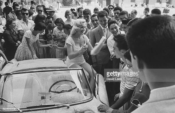 Singer Juli Reding sitting on her car while she signs autographs for her fans during her visit
