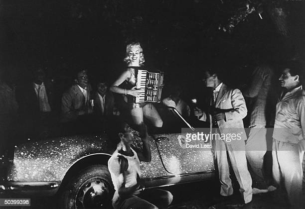Singer Juli Reding standing in her car as she plays the accordion for a group of fans standing around
