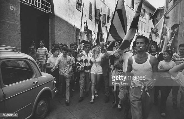Singer Juli Reding wearing shorts carrying an Italian flag while walking down the street wth a group of fans