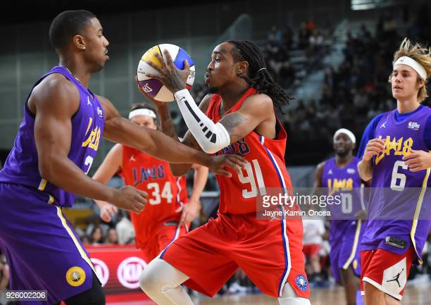 Singer Justin Beiber looks on as American rapper Quavo drives to the basket past actor Michael B Jordan during the 2018 NBA AllStar Game Celebrity...