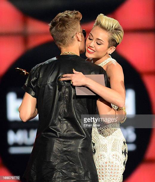 Singer Justin Bieber accepts the award for Top Male Artist presented by singer Miley Cyrus onstage during the 2013 Billboard Music Awards at the MGM...
