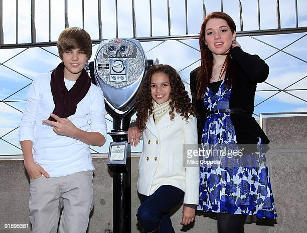 Singer Justin Bieber actress Madison Pettis and actress Jennifer Stone pose at the The Empire State Building in honor of Jumpstart's 4th Annual...