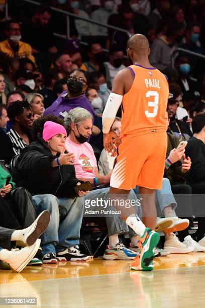 Singer Justin Bieber greets Chris Paul of the Phoenix Suns against the Los Angeles Lakers on October 22, 2021 at STAPLES Center in Los Angeles,...