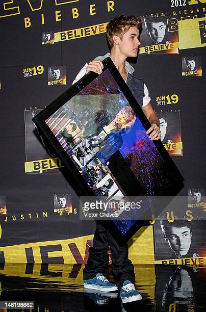 Singer Justin Bieber handling a recognition for more than 500000 sold copies of his catalog only in Mexico during a press conference and photocall at...