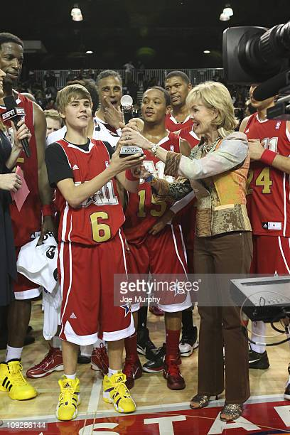 Singer Justin Bieber of the West is presented with the MVP award against the East during the BBVA 2011 NBA AllStar Celebrity Game on center court at...